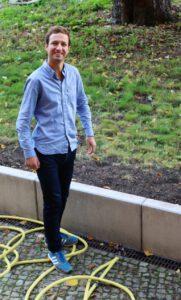 Junger Mann mit blauem Hemd, auf dem Boden gelber Gartenschlauch